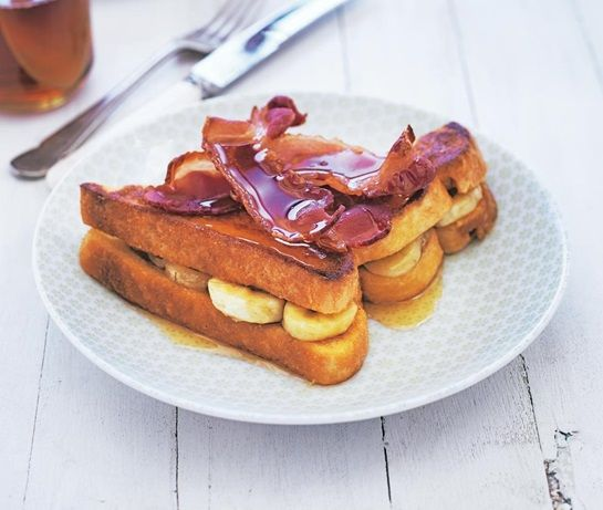 Fried eggy bread sandwich filled with slices of banana and topped with bacon then drizzled with maple syrup