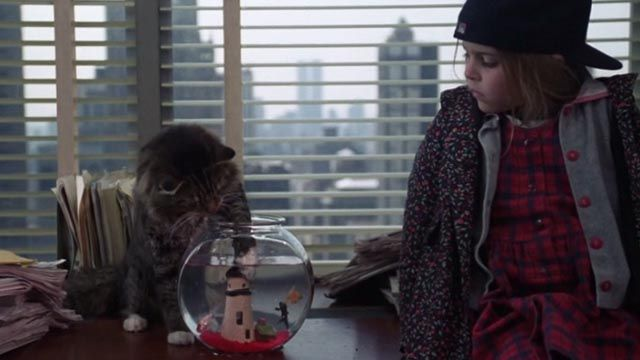 A Maine Coon tabby cat named Lois Lane helps herself to a sushi lunch as Maggie (Mae Whitman) watches in the romantic comedy One Fine Day (1996).
