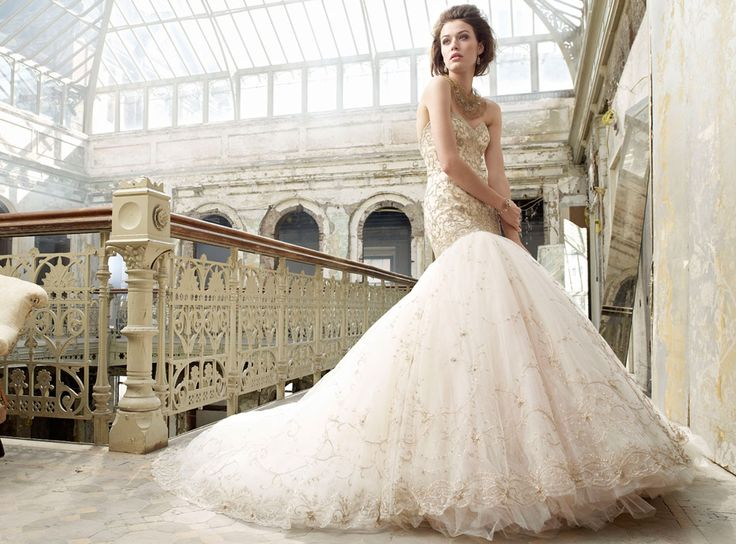 Gold embroidered English net over sherbet tulle bridal ball gown, sweetheart neckline, elongated bodice with circular skirt, chapel train.