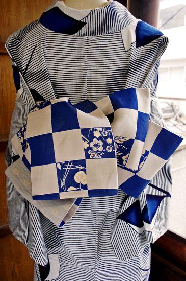紺青とグレーのレトロモダンな市松模様に、松葉や葵の葉、梅の花枝や菊花の模様がクラシカルな情緒をプラスしてくれている粋な半幅帯です。