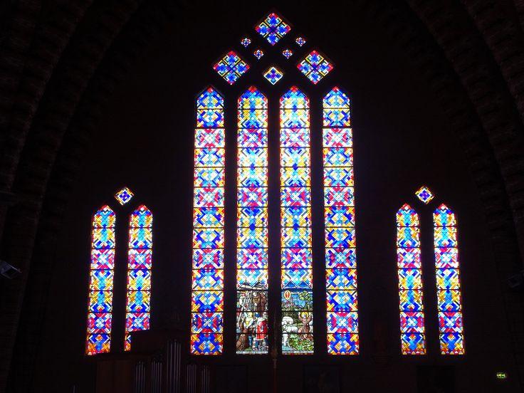 Bolsward - Friesland - St. Franciscuskerk. Deze rooms-katholieke kerk is een in 1932 ontworpen gebouw in een expressionistische art-decostijl.  De twee grote en tegenover elkaar liggende nieuwe gebrandschilderde ramen bevatten ook delen van de uit de oude kerken afkomstige voorstellingen. De kerk werd op 8 mei 1934 ingewijd. foto: G.J. Koppenaal - 10/8/2016.