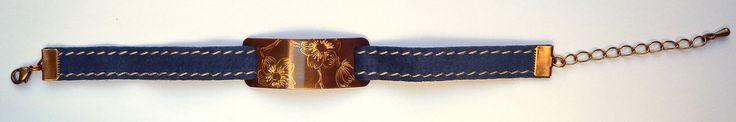 Bracelet en cuir bleu serti d'une plaque en laiton, gravée de fleurs de cerisier.