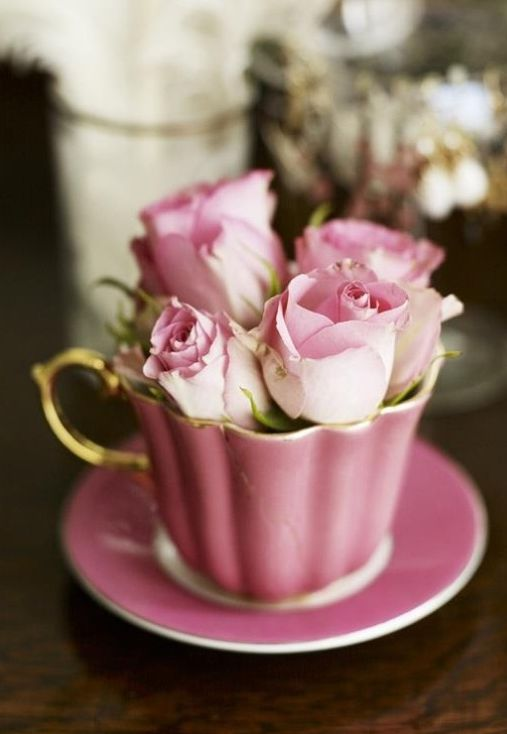 Pink teacup filled with pink rose buds.