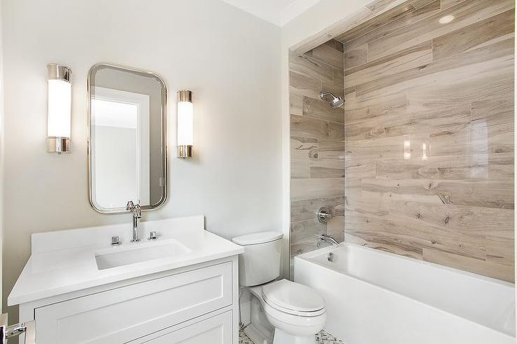 White cottage bathroom is equipped with a white dresser-like washstand fitted with a white countertop and backsplash and a polished nickel faucet positioned beneath a curved vanity mirror flanked by frosted glass wall sconces.