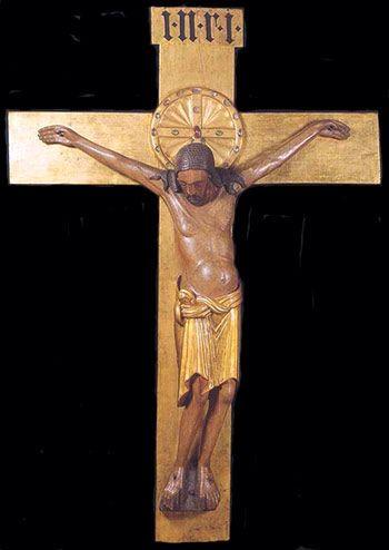 """Houten Gero-kruis (naar aartsbisschop Gero) Keulen Dom 976.  Jezus zakt door en het hoofd valt zijwaarts naar voren. Monumentale houten kruizen met een dode of lijdende Christus, (die meestal een lendendoek draagt), de zogeheten Christus patiens (Latijn voor """"Lijdende Christus""""), is tamelijk zeldzaam en zelfs in dat geval wordt de doodssmart niet in volle heftigheid getoond, zoals in de latere Gotiek. Deze voorstellingen zijn meer bedoeld om niet enkel de verering maar ook het mede-lijden…"""