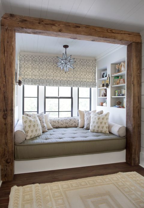 Frame a cozy bay window nook with dark rustic wood, like CLOTH & KIND does here, to add a rustic touch to modern, neutral-toned interiors.