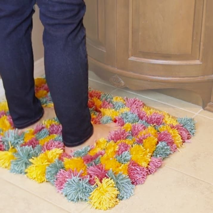 This Fluffy Pom-Pom Rug Is Cozy AF  To seal the pom poms buy a can of liquid rubber and paint the backside of the rug.   Also wash it inside of a pillow case to protect the pom poms.