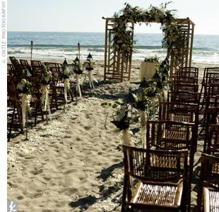 Bamboo chairs, arranged in an arc, set the tone for a tropical-inspired wedding. Iron lanterns and scattered white rose petals denoted the aisle, while a garden trellis covered with tropical blooms and flanked by tiki torches served as the altar. The site faced the waves of the Pacific Ocean just before sunset.
