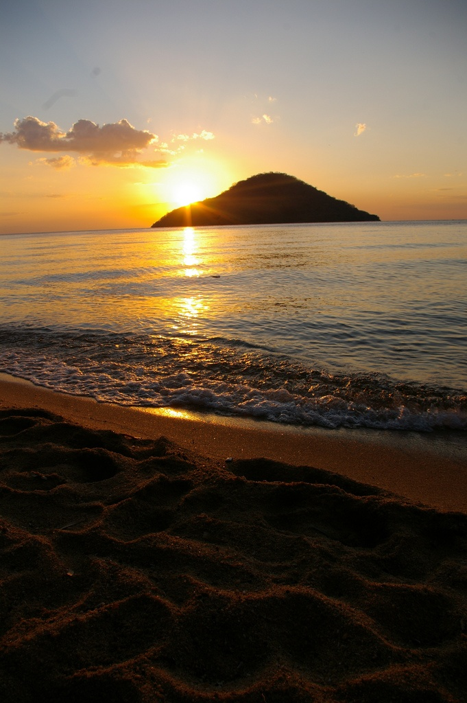 Sunset at the beautiful Lake Malawi (also known as Lake Nyasa).  This lake, the third largest in Africa and the eighth largest lake in the world, is located between Malawi, Mozambique, and Tanzania. It is the second deepest lake in Africa, although its placid northern shore gives no hint of its depth. #travel #lake #Malawi