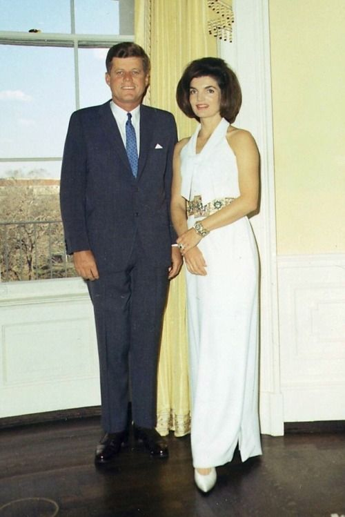 Jackie and President John F. Kennedy pose for photo in the Yellow Room of the White House on March 28, 1963. Jackie is wearing an white crepe sleeveless halter gown designed by Oleg Cassini. Along with a belt given to her by King Hassan II of Morocco during his visit to the White House.