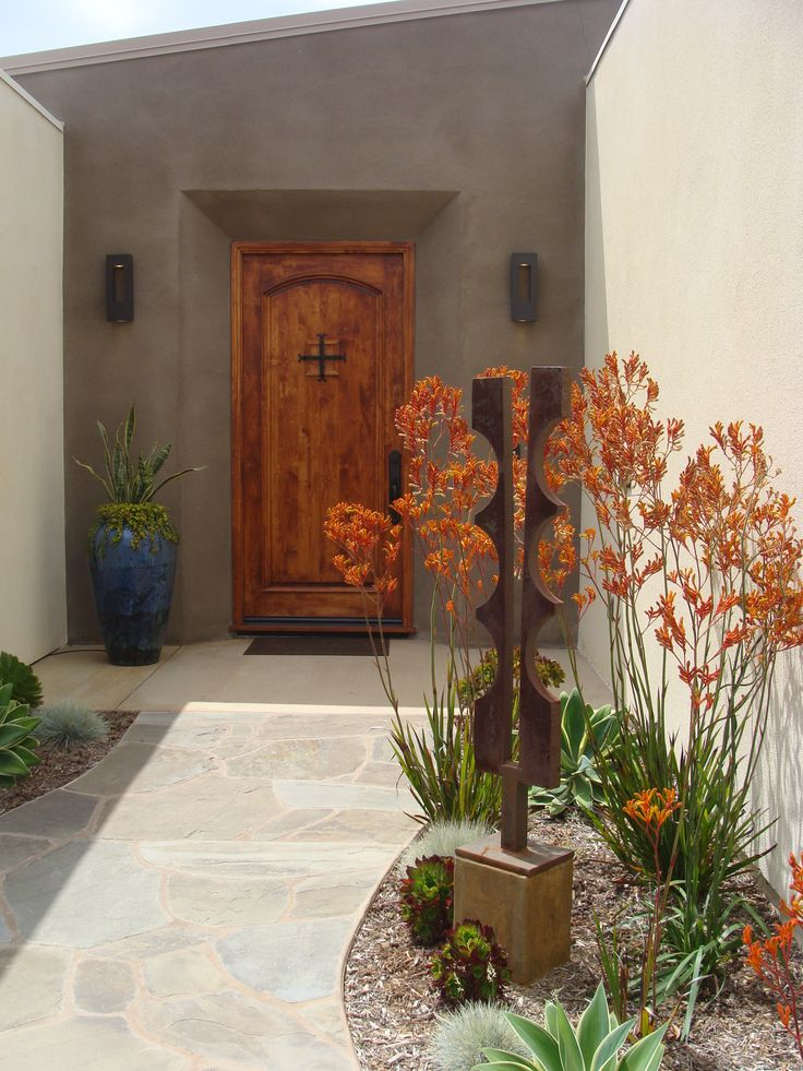 The colors of the flowers, sculpture, door and large urn combine beautifully. And the architecture of the tall wands of Kangaroo Paws silhouetted against the light colored wall make this a terrific design. A bit of night lighting would make it over-the-top.