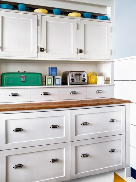 Shaker-style fronts hide two sets of refrigerator and freezer drawers. The cabinets above conceal small appliances. Chrome latches and pulls and horizontally planked walls complete the casual farmhouse look. |   Photo: Bruce Buck | thisoldhouse.com