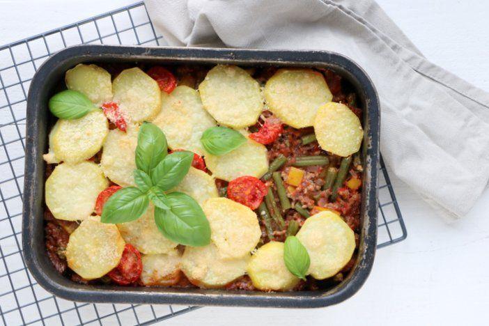Een ovenschotel met sperziebonen en gehakt kan het hele jaar door wat mij betreft wel. Met extra groenten en een dakje van aardappel en parmezaanse kaas.