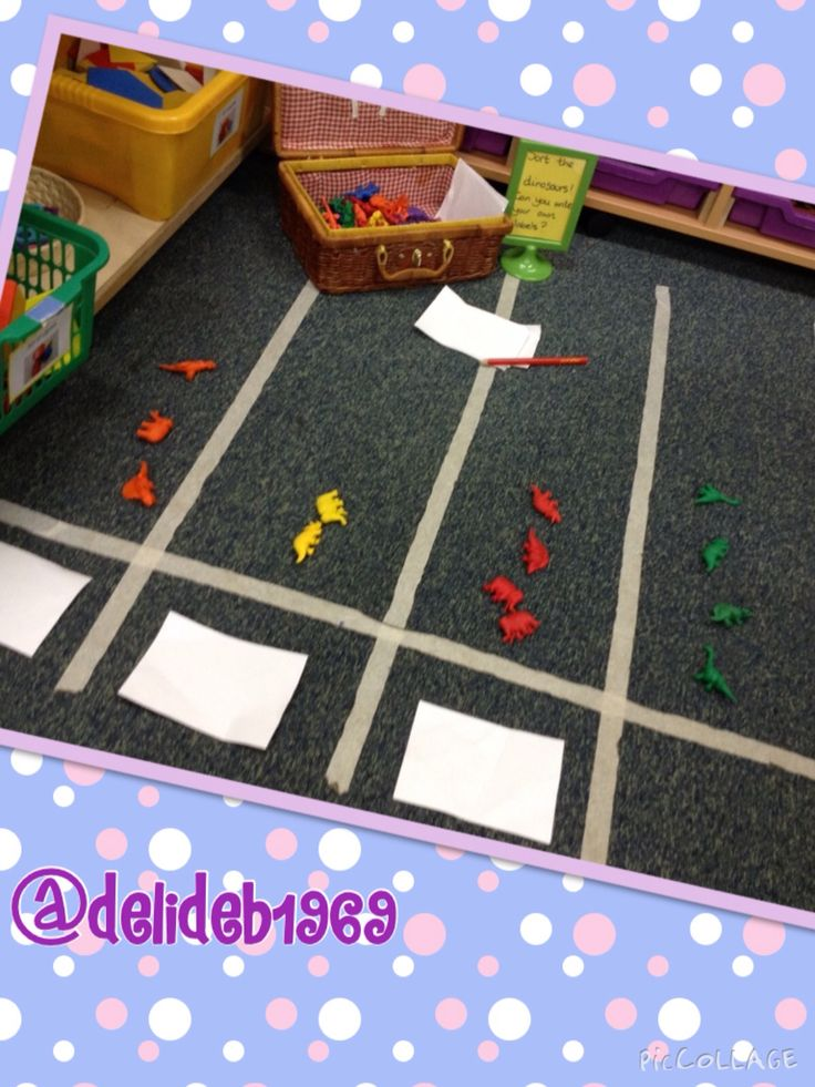 Boy friendly dinosaur sorting on a floor based pictogram. Paper and pencils available to encourage labelling criterion.