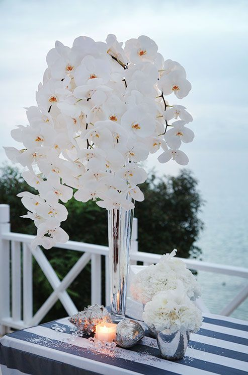 Hardy white orchids in tall metallic vases hover over white blooms and silver objet.