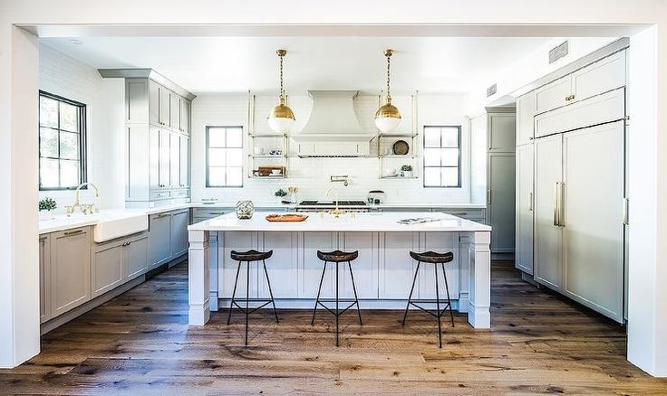 White and gray kitchen features two brass Hicks pendants illuminating a gray center island topped with white quartz fitted with a farmhouse sink and brass gooseneck faucet lined with iron and wood backless bar stools.