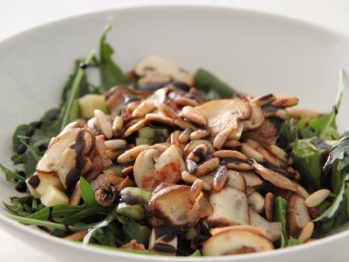 Rucolasalat mit gebratenen Champignons und Pinienkernen.