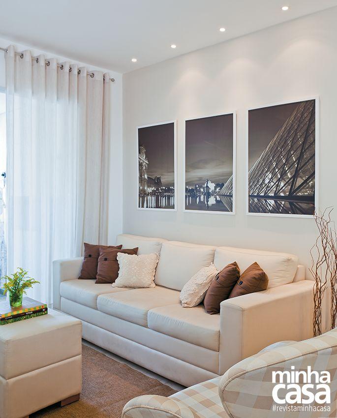 quadros em cima do sof e almofadas marrom