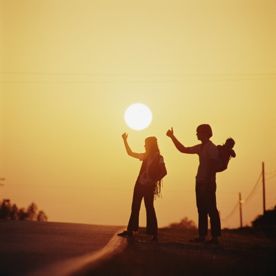 Silhouetted Couple Hitchhiking on Empty Road  Trampen