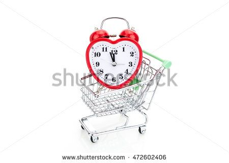 Shopping cart with alarm clock in shape of a heart, isolated on white background