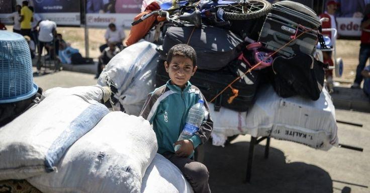 20150617 - Um menino sírio espera entre pertences do lado turco da fronteira com a Síria antes de voltar para a cidade síria de Tal Abyad. Os primeiros refugiados iniciaram a volta para casa após a cidade ter sido tomada pelos curdos, que expulsaram o EI (Estado Islâmico). Os combates levaram 23 mil pessoas a deixarem a região  PICTURE: Bulent Kilic/AFP