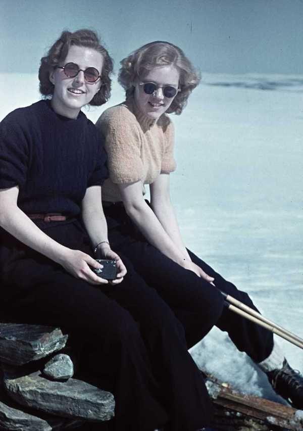 1941. Skidåkning. Två kvinnor med solglasögon sitter vid ett stenröse. color found photo print ladies in pants and short sleeve blouse sweater sunglasses day casual sportswear 40s war era