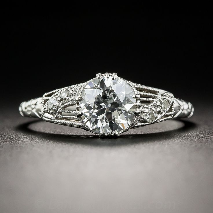 A splendid and resplendent original Art Deco low-profile finger-hugger, beautifully die-struck and hand finished in platinum, circa 1920s-30s, presents a gorgeous icy-white European-cut diamond, weighing 1.13 carats.  The scintillating stone is elegantly embellished on each side with pierced mirror-image design motifs aglitter with pairs of small round diamonds leading to a decoratively embossed ring shank. A lovely gallery design and delicate milgraining add the finishing touches to this…