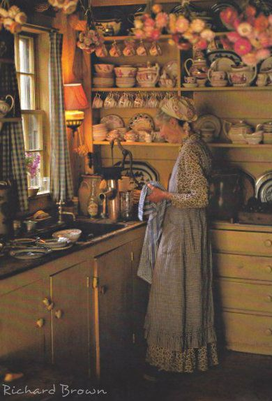 Tasha in her kitchen... notice the dried flowers above and although she has a faucet...the pump for her water.