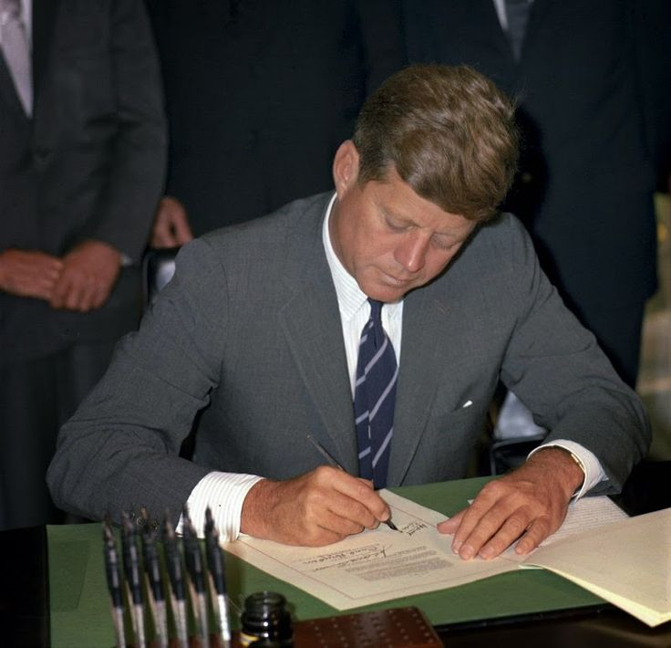 Twenty-nine days before his death, President John F. Kennedy signs the  Maternal and Child Health and Mental Retardation Planning Bill  in the Oval Office (October 24, 1963).