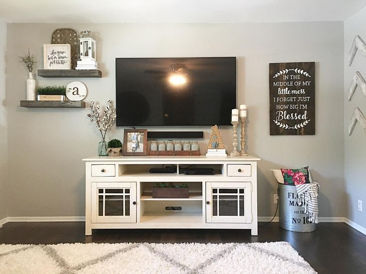 Living Room, family room, tv room, living room decor, family room decor, farmhouse style, farmhouse decor, modern farmhouse, farmhouse living room, white tv console, tv console, tv console decor, media console, media console decor, white rug, throw pillows, throw blanket, cotton stems, Mason jars, candle sticks, galvanized tin, tv, wooden sign, floating shelves, shelf decor, faux greenery, split level living room, open concept, living room Remodel,