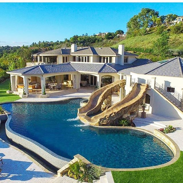 A luxurious swimming pool with two slides. Great backyard for a party!