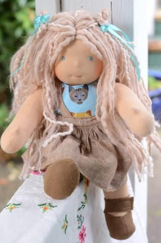 This is Alexia. She has sunkissed skin and blue eyes. Her hair is made with various wool and mohair yarns with a highlight through it. Alexia comes with the p