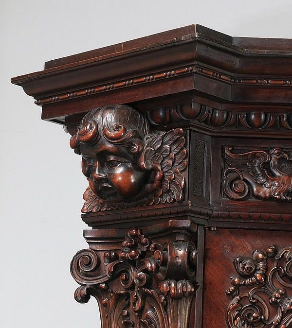 19th century highly carved tripartite bookcase in the Venetian Baroque taste, executed in walnut, having a rectangular top with projecting canted corners, above egg and dart molding and a running frieze centering a male mask flanked by putti masks, surmounting a three door case, the center door having a sculptural carving of the goddess Minerva in an arched shell niche with a carved owl keystone, hovering putti, and musical trophy columns, Minerva, goddess of wisdom and healing, wearing a…