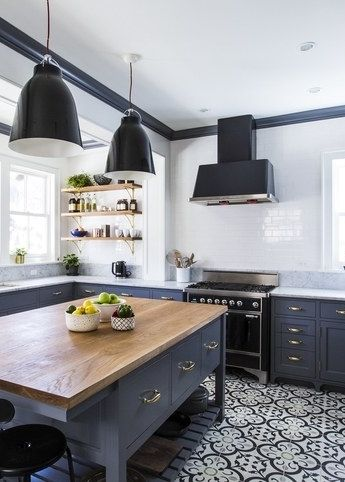 Custom tiles, a large island, and open shelves make for one chic kitchen.