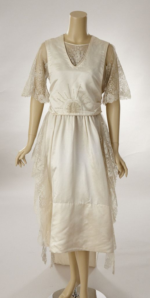 1917 White silk satin wedding dress with long train. The dress is ornamented with beautiful French lace and embroidered with small pearls. There are two pearls missing from the center front bodice decoration. The dressmakers pencil marks as to where to place the pearls can still be seen.  The lace is used across the upper bodice and short sleeves. Draped panels of matching lace are placed right and left of the side seams. Front