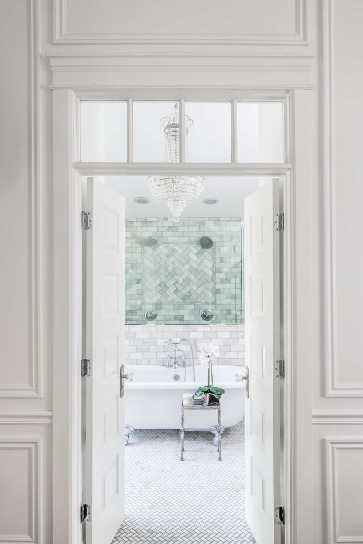 Elegant entry to a classic white bathroom. French doors with interior transom and paneled molding open to a marble bath with clawfoot tub and empire style crystal chandelier. Design by The Fox Group. #elegantdecor #bathroomdesign #traditionalstyle #classicbathroom #frenchdoors