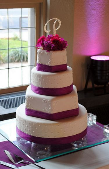 Four tier round and hexagonal white wedding cake with magenta bands and flowers and crystal monogram topper.JPG