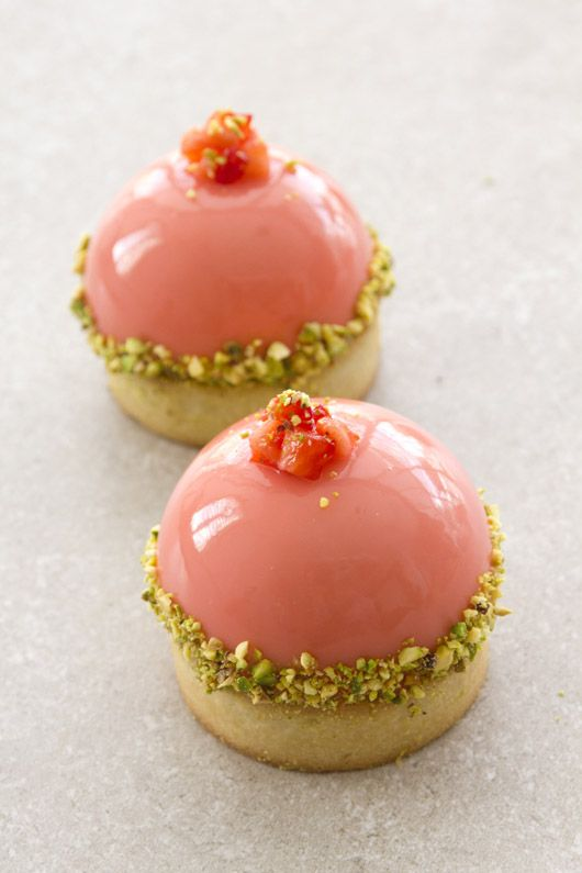 Dome with pistachio cream, strawberry mousse, and pink white-chocolate glaze on a crispy pastry crust. Garnished with chopped roasted pistachios and fresh strawberries.