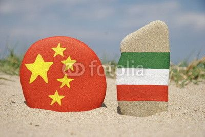 China and Italy flags on stones with sand background