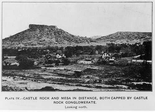 """ACCESSION NUMBER: 1992.001.0678.0109aa  PHOTOGRAPHER:  George Burr Richardson  TITLE:  Plate IV.--Castle Rock and mesa in the distance, both capped by Castle Rock Conglomerate.  DESCRIPTION:  Photographs and maps from: Geologic Atlas of the United States, Castle Rock Folio, Colorado (N151). United States Geological Survey, 1915. Looking north toward the town of Castle Rock and """"The Rock"""", the geological formation, a large rock atop a pyramid shaped hill. Buildings, fences, trees are..."""