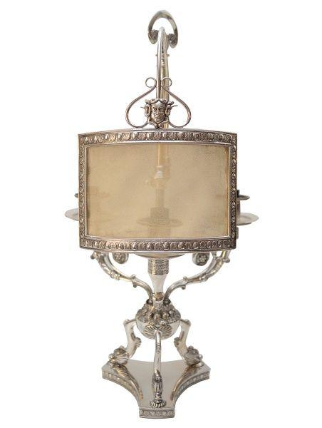 Luminária de mesa executada em prata de lei italiana, contraste 800 mm. Composta por três luzes sustentadas por braços recurvos, que se apoiam ao fuste. Este último esférico lavrado por elementos fitomorfos e apoiados sobre base tripoide zoomorfa. Itália. Século XIX. 46 cm.