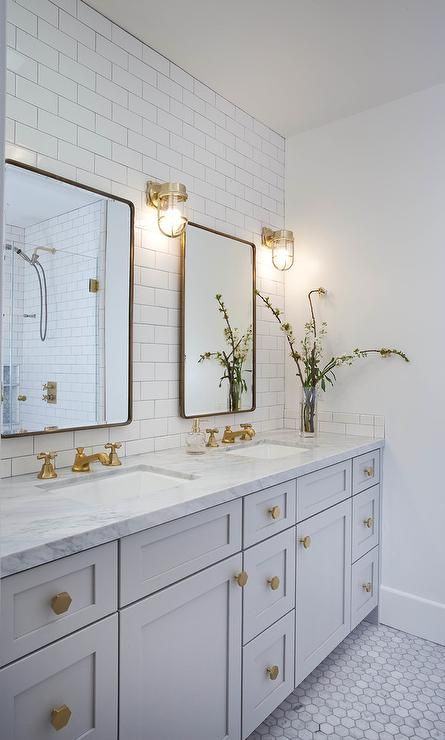 Well appointed light gray and white basement bathroom features two Restoration Hardware Bristol Flat Mirrors mounted on white subway backsplash tiles and illuminated by brass cage wall sconces.