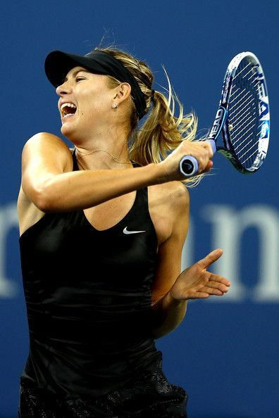 Maria Sharapova Photos - Maria Sharapova of Russia returns a shot to Sabine Lisicki of Germany during their women's singles second round match on Day Five of the 2014 US Open at the USTA Billie Jean King National Tennis Center on August 29, 2014 in the Flushing neighborhood of the Queens borough of New York City. - US Open: Day 5