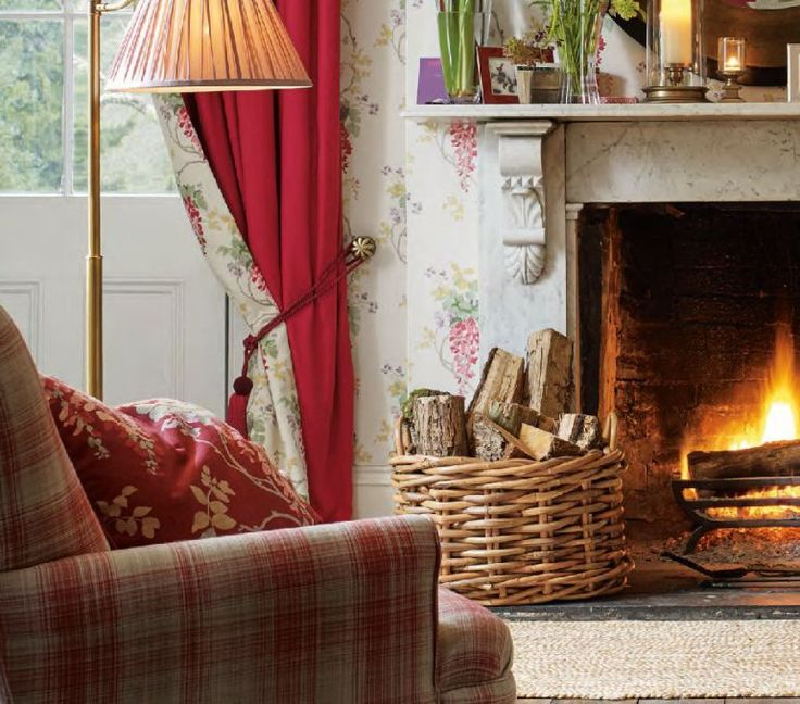 Cottage living room with open fire, basket of logs and a comfy armchair.