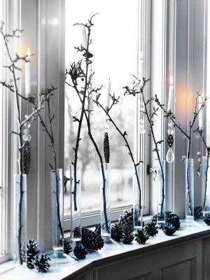 Takken in smalle vazen voor het raam.