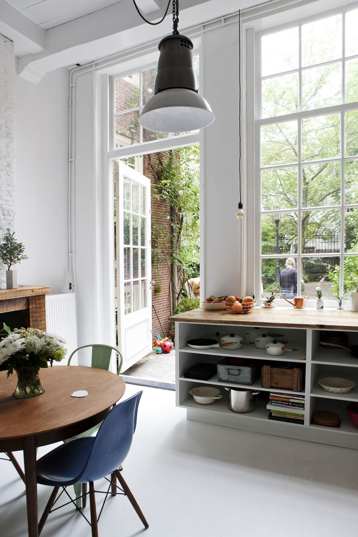 Open dining space with large windows, an industrial pendant light