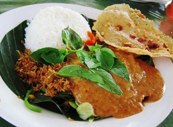 Nasi pulen yang hangat dan pecel Madiun disajikan dalam pincuk daun pisang.