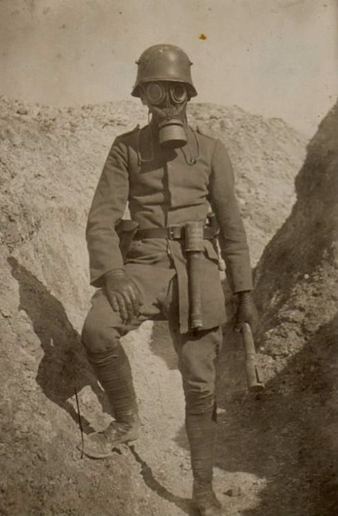 WW1: German storm trooper poses in the trenches with gas mask and potato masher hand grenades. His job was to rush enemy trenches, usually at night, and establish possession for the infantry wave to take over.