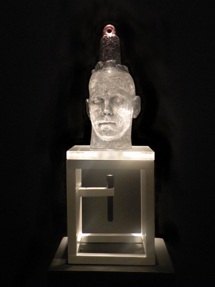 CLIFFORD RAINEY - Sore Head  2012  Cast glass, steel sculpture stand, Mag-Lite