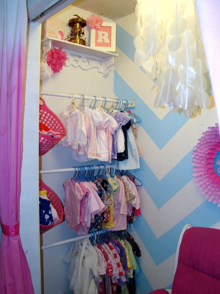 Tension rods across one end of the closet for her clothing, rest of the closet for play!